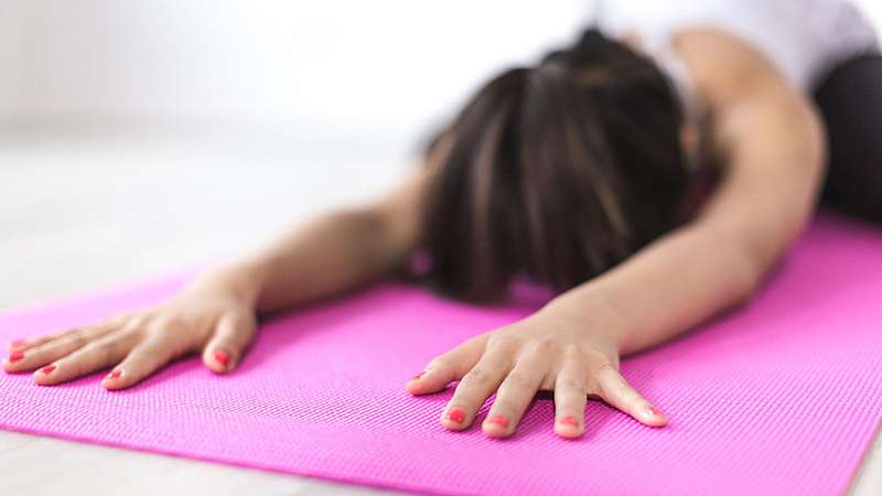 Frau in Child's Pose auf Yogamatte